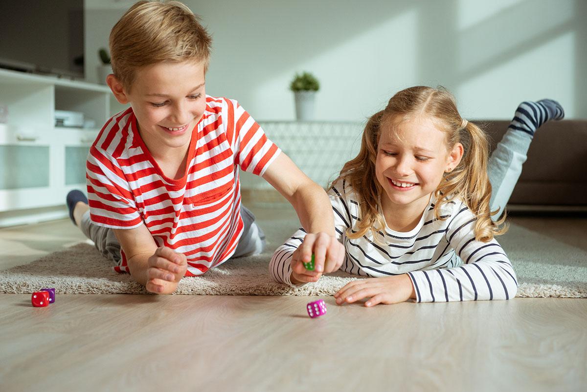 Niños jugando en el suelo de su casa climatizada con energía renovable y suelo radiante